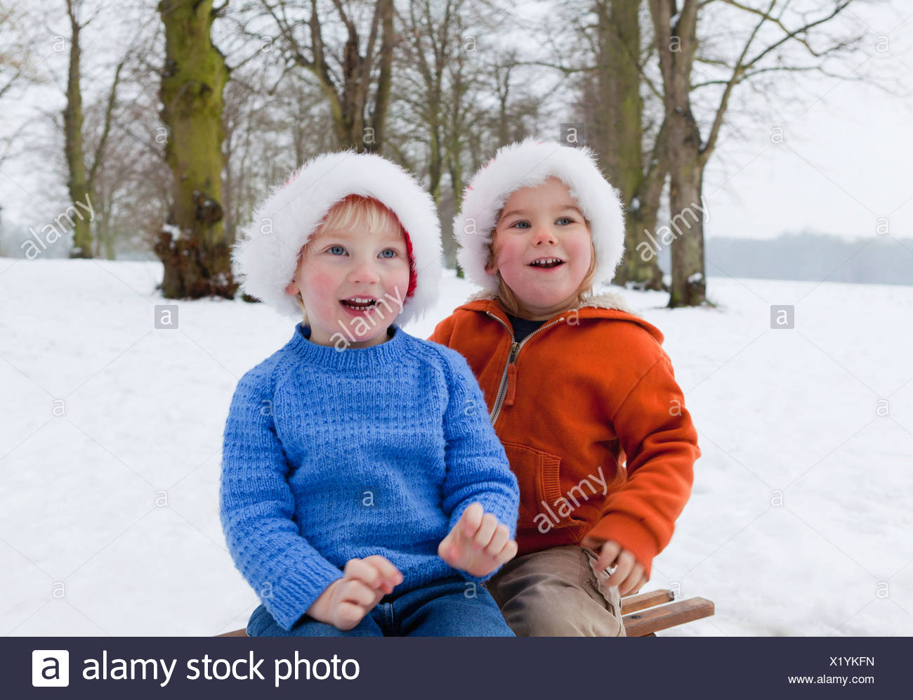 Two boys wearing fluffy hats in the snow - Stock Image