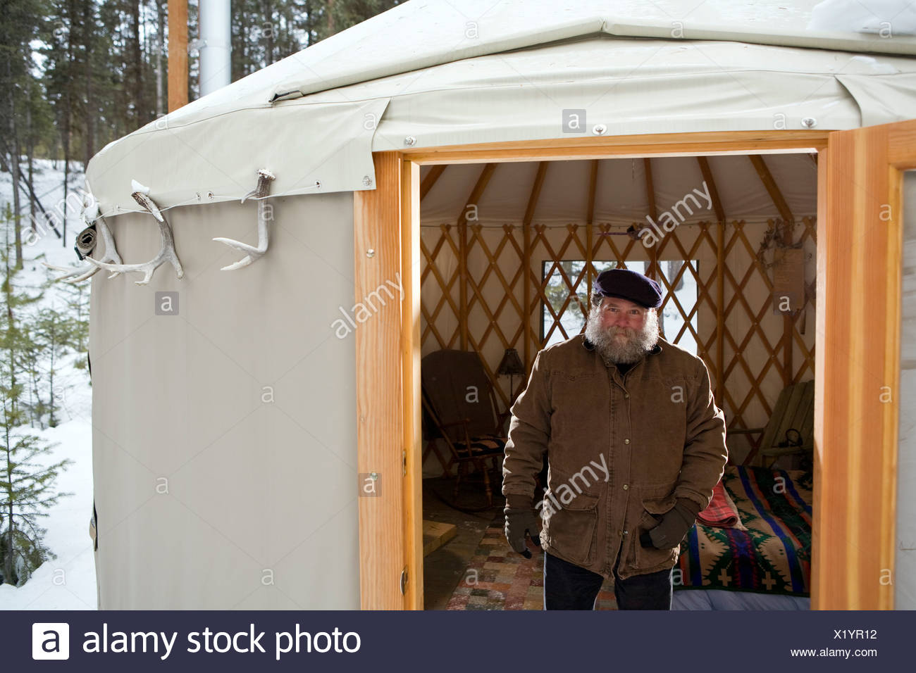Bearded man with hat in sparse yurt, Whitefish, Montana