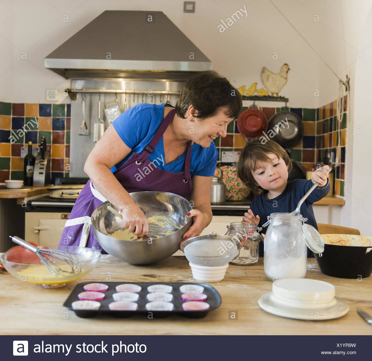 A woman and a child cooking at a kitchen table, making fairy ...