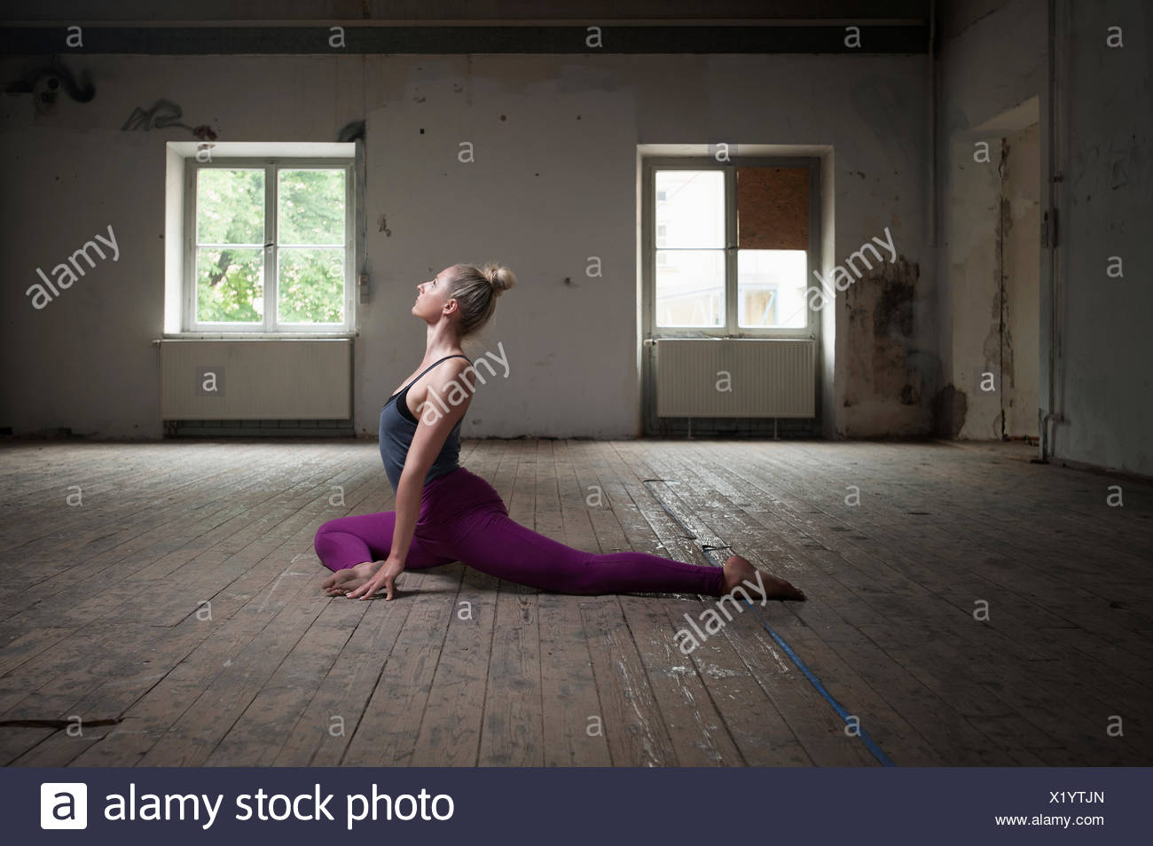 Mid adult woman practicing pigeon pose in yoga studio, Munich, Bavaria, Germany - Stock Image