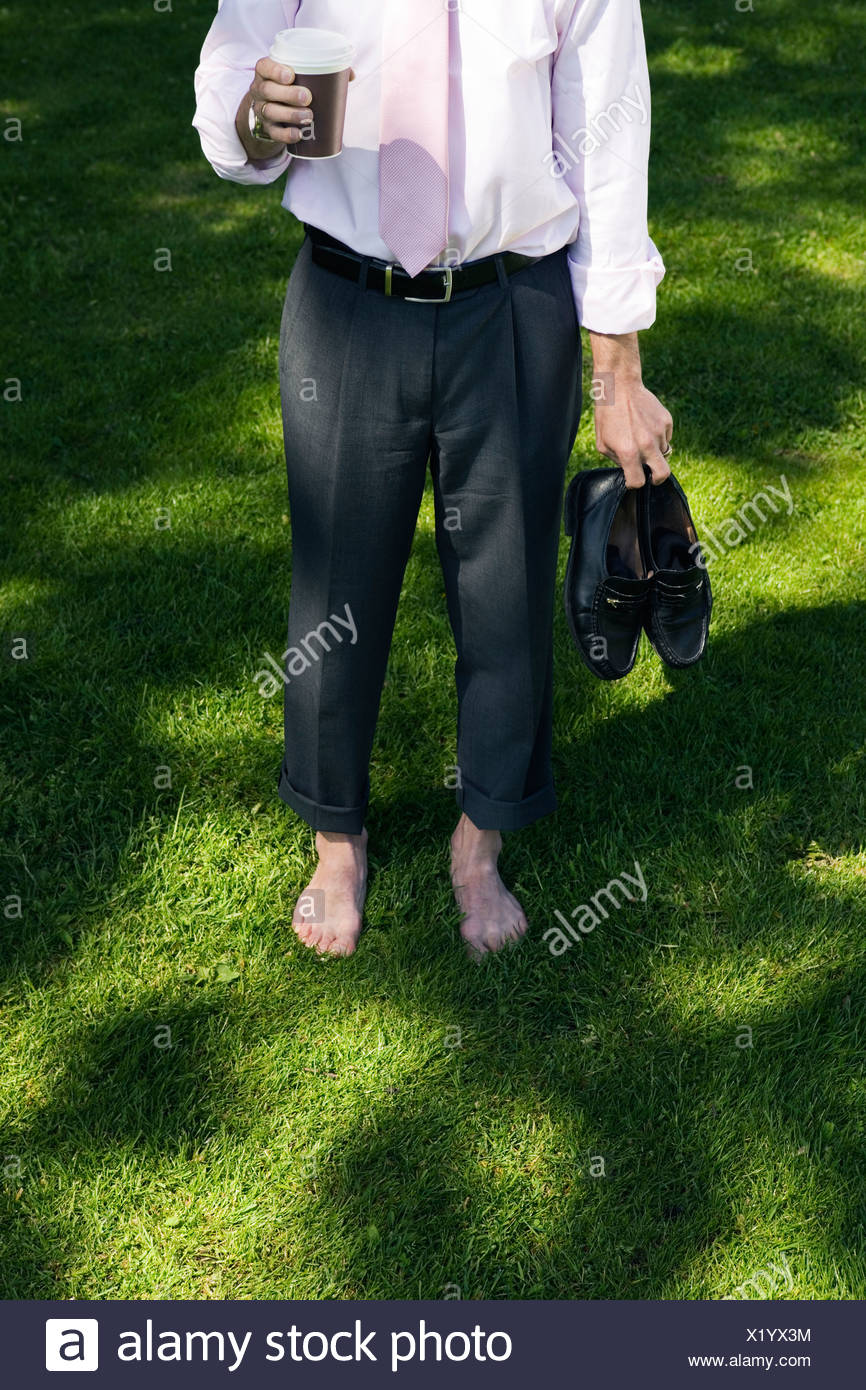A barefooted businessman standing on the grass, Stockholm, Sweden. - Stock Image