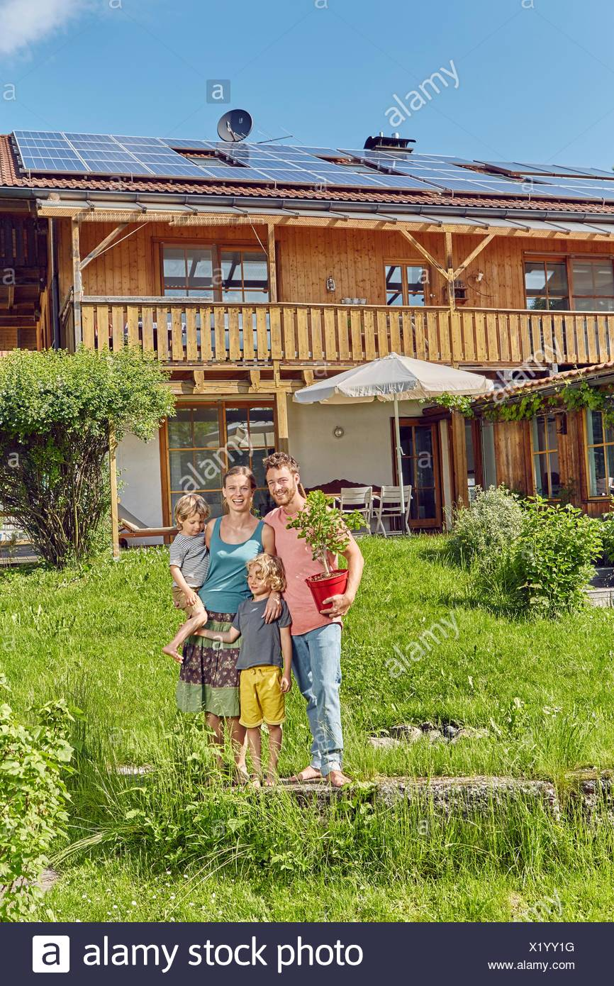 Portrait of young family, holding pot plant, standing in front of house with solar panelled roof - Stock Image