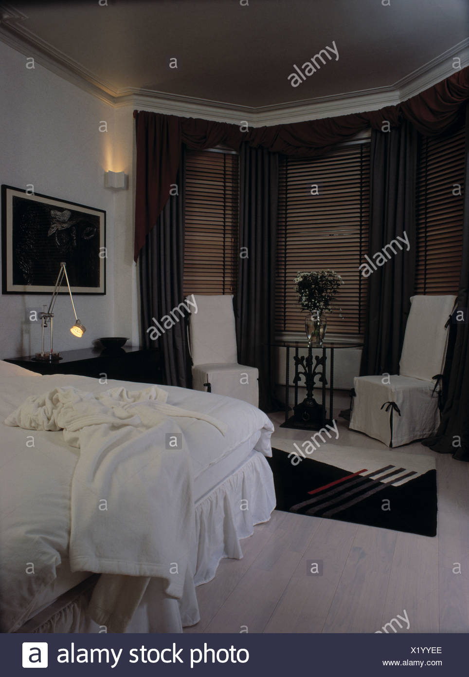 White loosecovers on chairs in front of bay window with ...