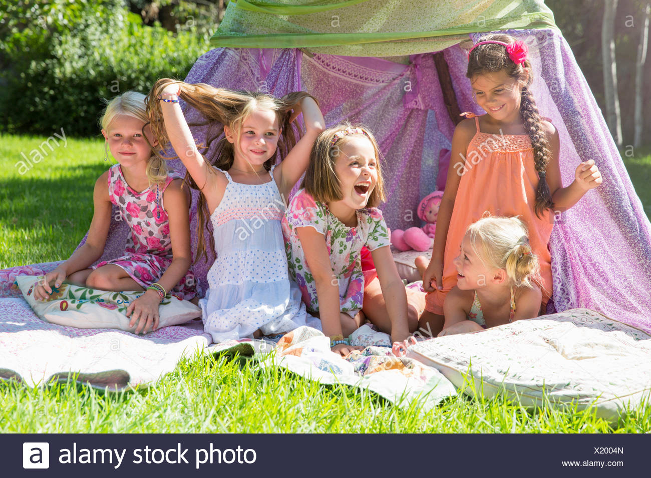 Five girls playing in garden teepee - Stock Image