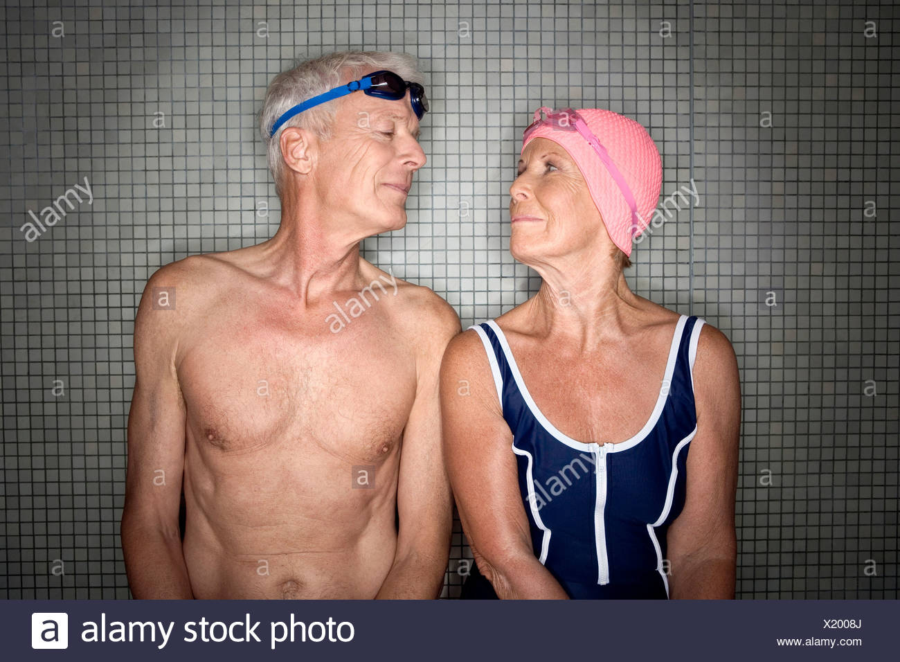 Senior couple in changing room, wearing swim cap and goggles Stock Photo