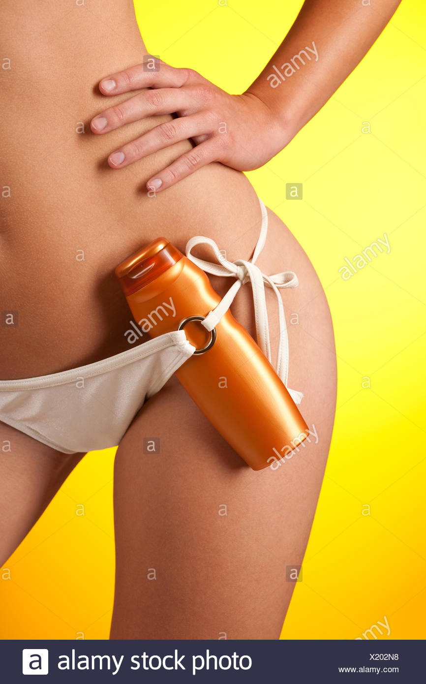 Part of female body with white bikini and bottle of suncream - Stock Image