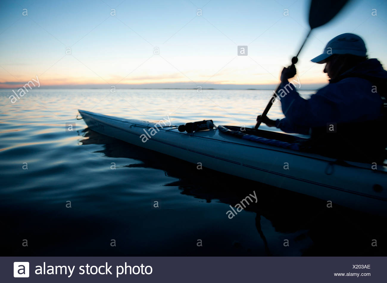 Person in nautical vessel oaring - Stock Image