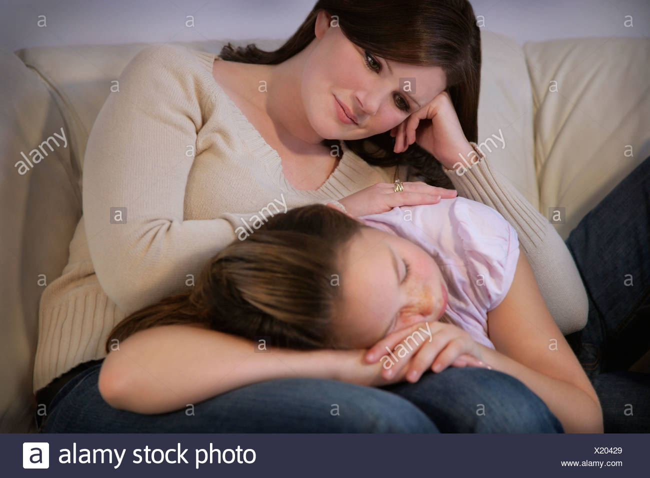 Mother watches tenderly over daughter - Stock Image