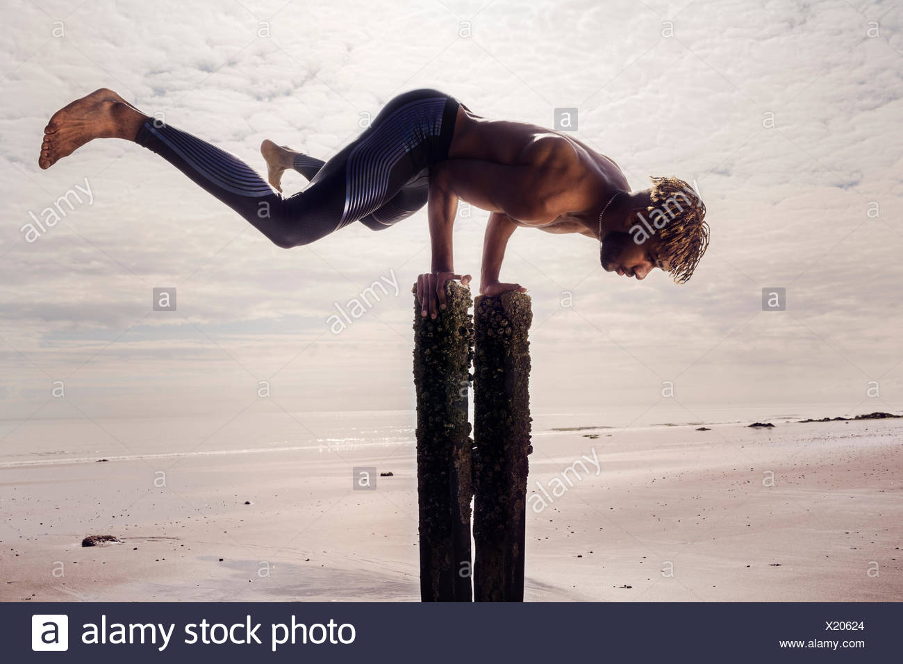 Young man training, doing handstand on wooden beach posts - Stock Image