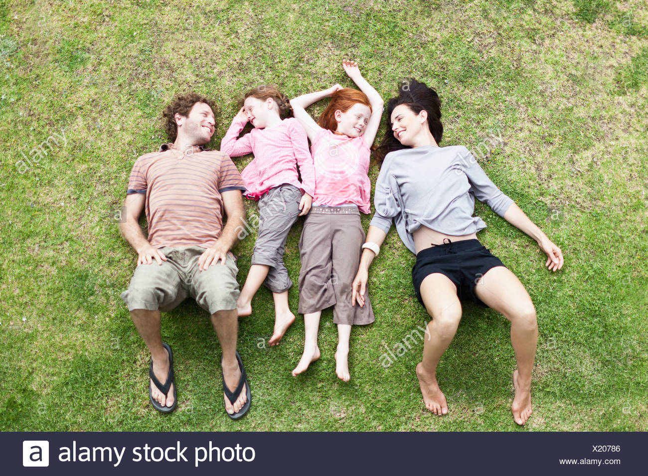Family laying in grass together - Stock Image
