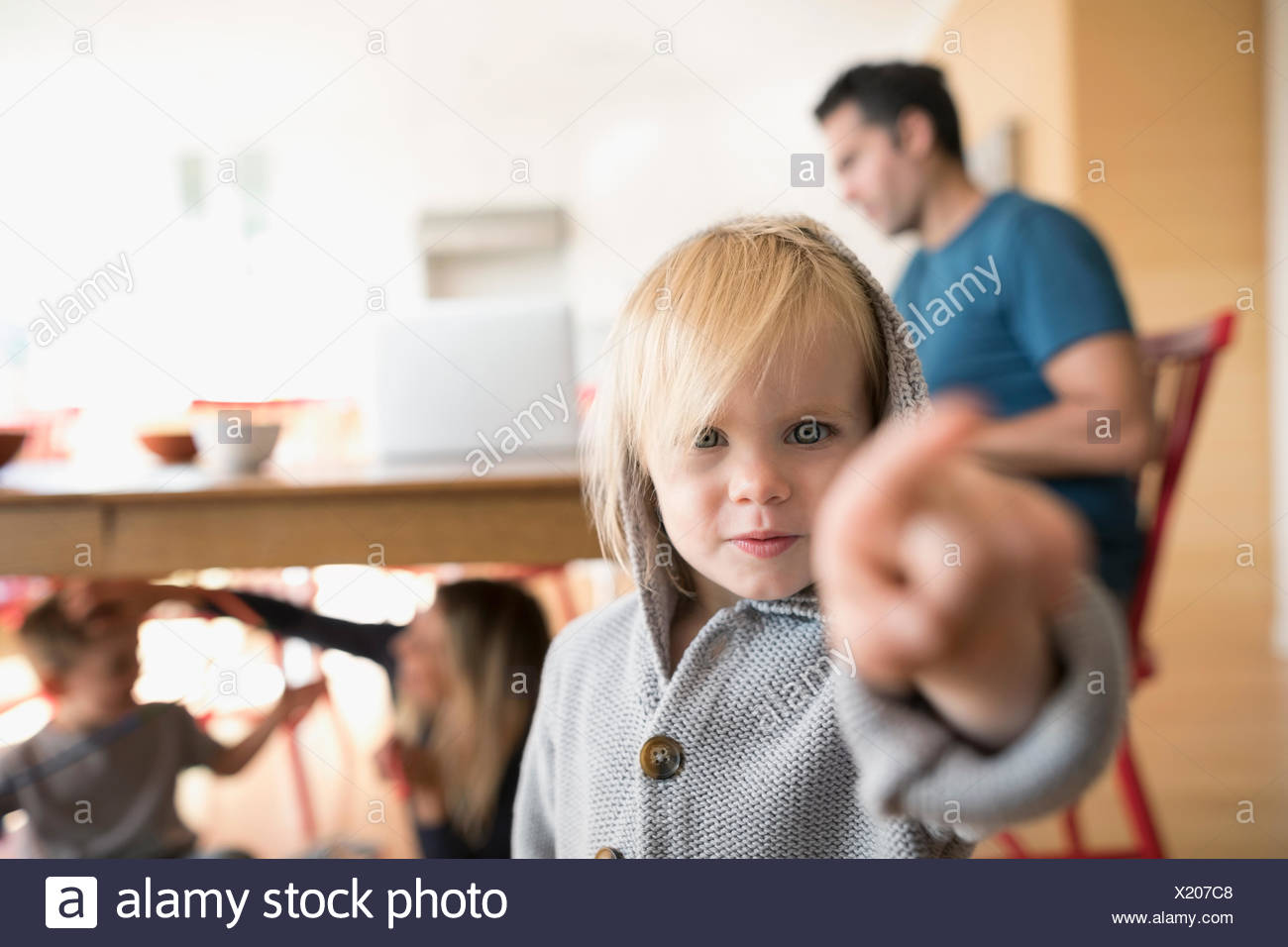 Portrait serious blonde toddler girl pointing - Stock Image