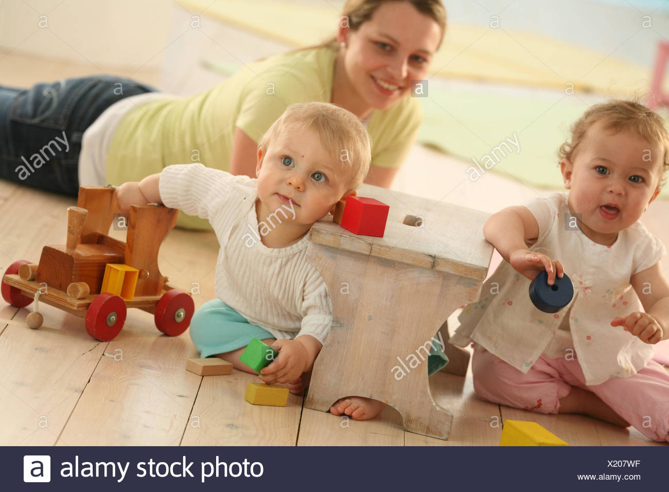 Babies, 9 months, mother, play, wooden toys, toys, dress, blond, discoveries, friends, reach, group, Indoor, boy, person, woman, girl, toys, fun, footstool, wooden locomotive, - Stock Image
