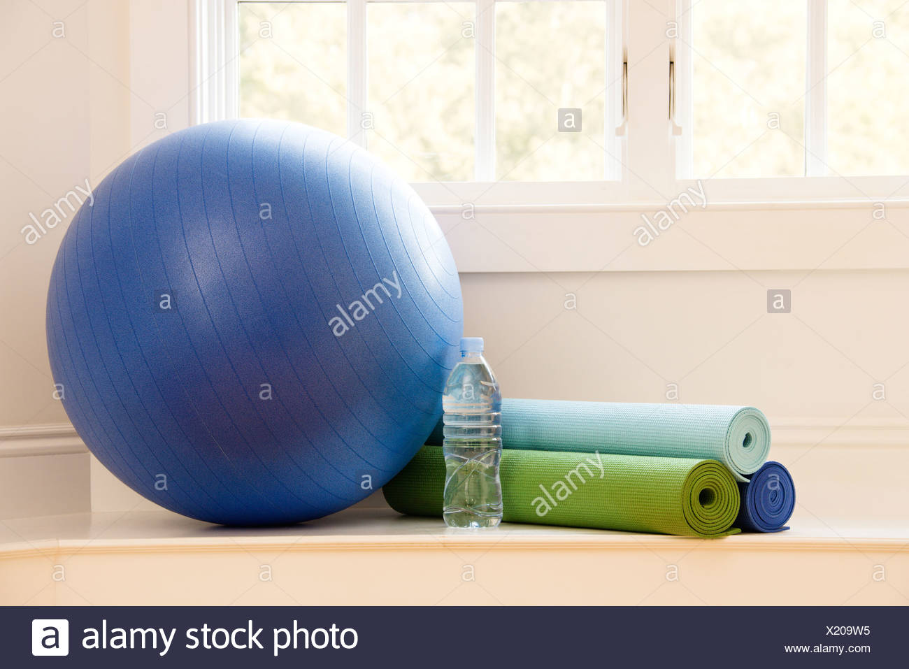 Balance ball exercise mats and bottled water at gym by window - Stock Image