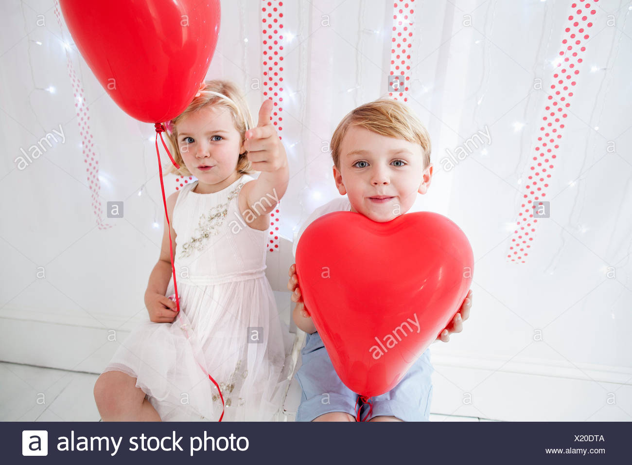 Young boy and girl posing for a picture in a photographers studio, holding red balloons. - Stock Image