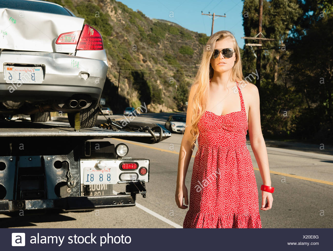 Young woman looking at camera as tow truck takes away damaged car - Stock Image