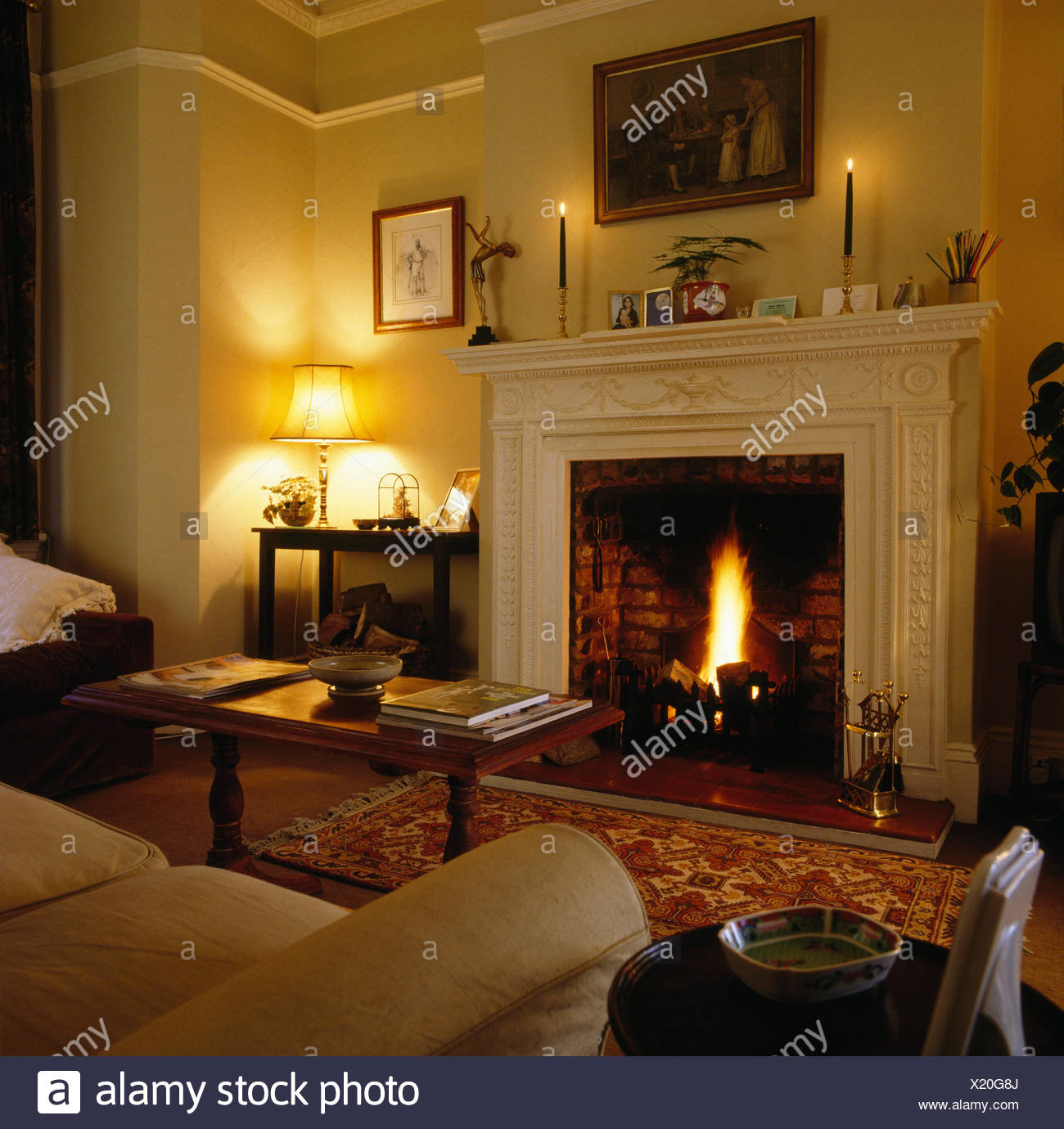 Lighted fire in fireplace in eighties living room with lighted lamp and candles - Stock Image