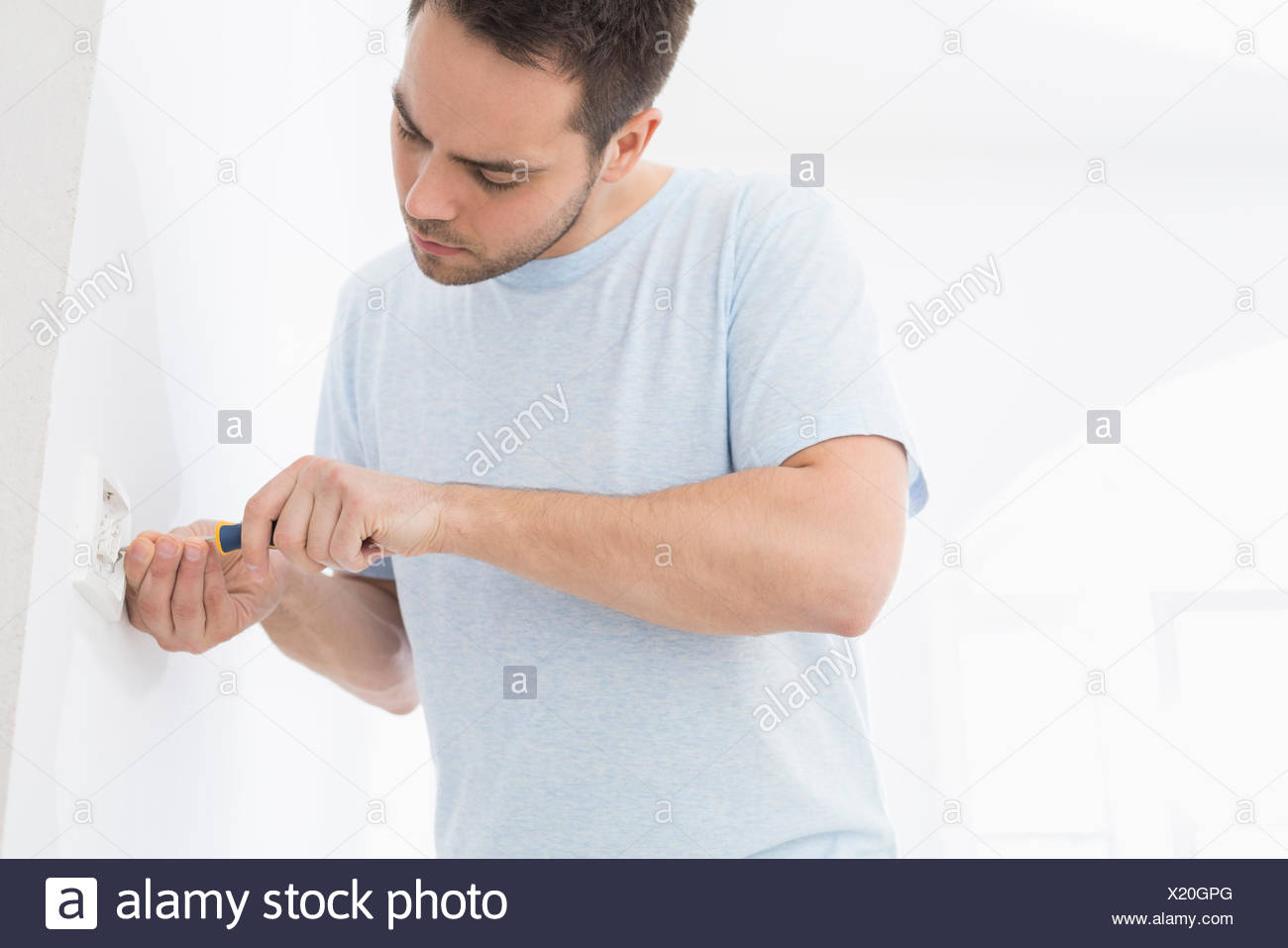 Man working on electrical outlet - Stock Image