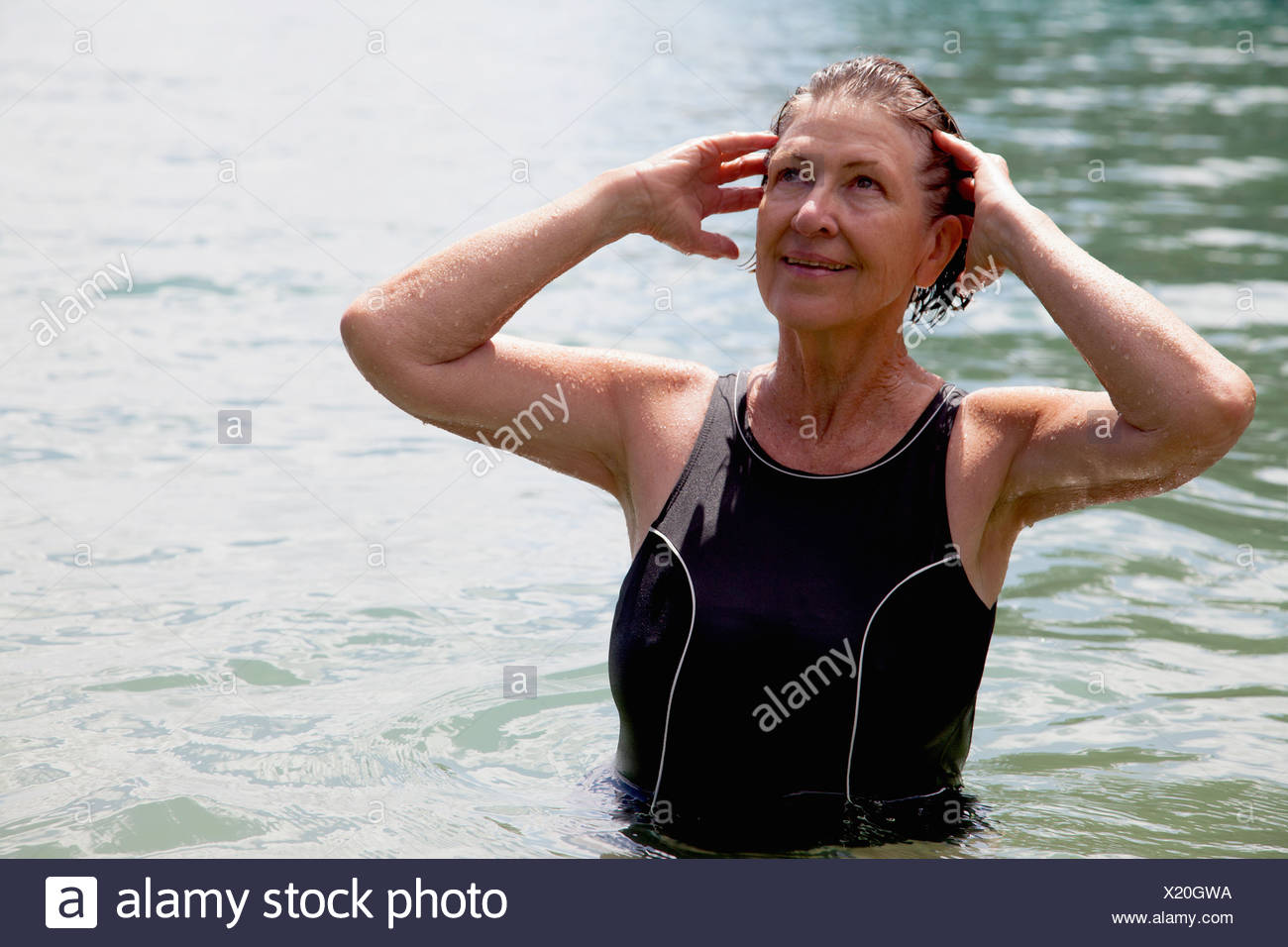 Senior woman swimmer with hands in wet hair - Stock Image