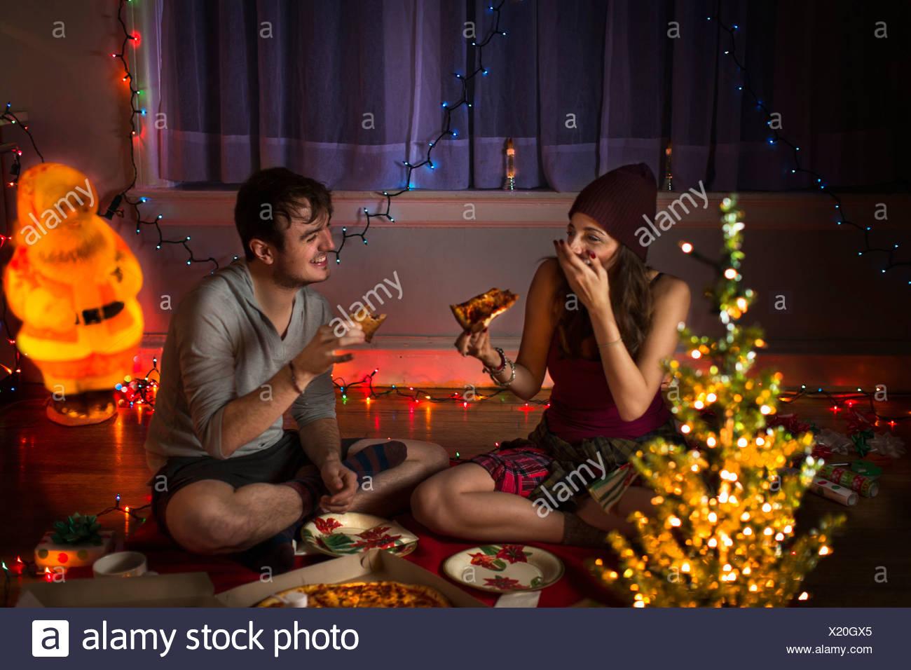 Young couple enjoying pizza at christmas - Stock Image