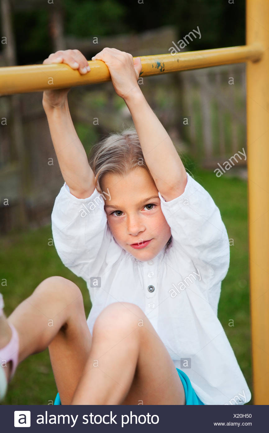Girl hanging on metal bar - Stock Image