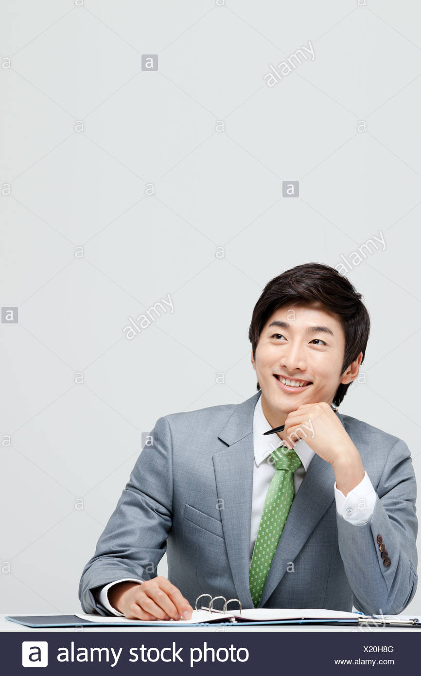 Portrait Of Smiling Asian Businessman At Desk With File - Stock Image