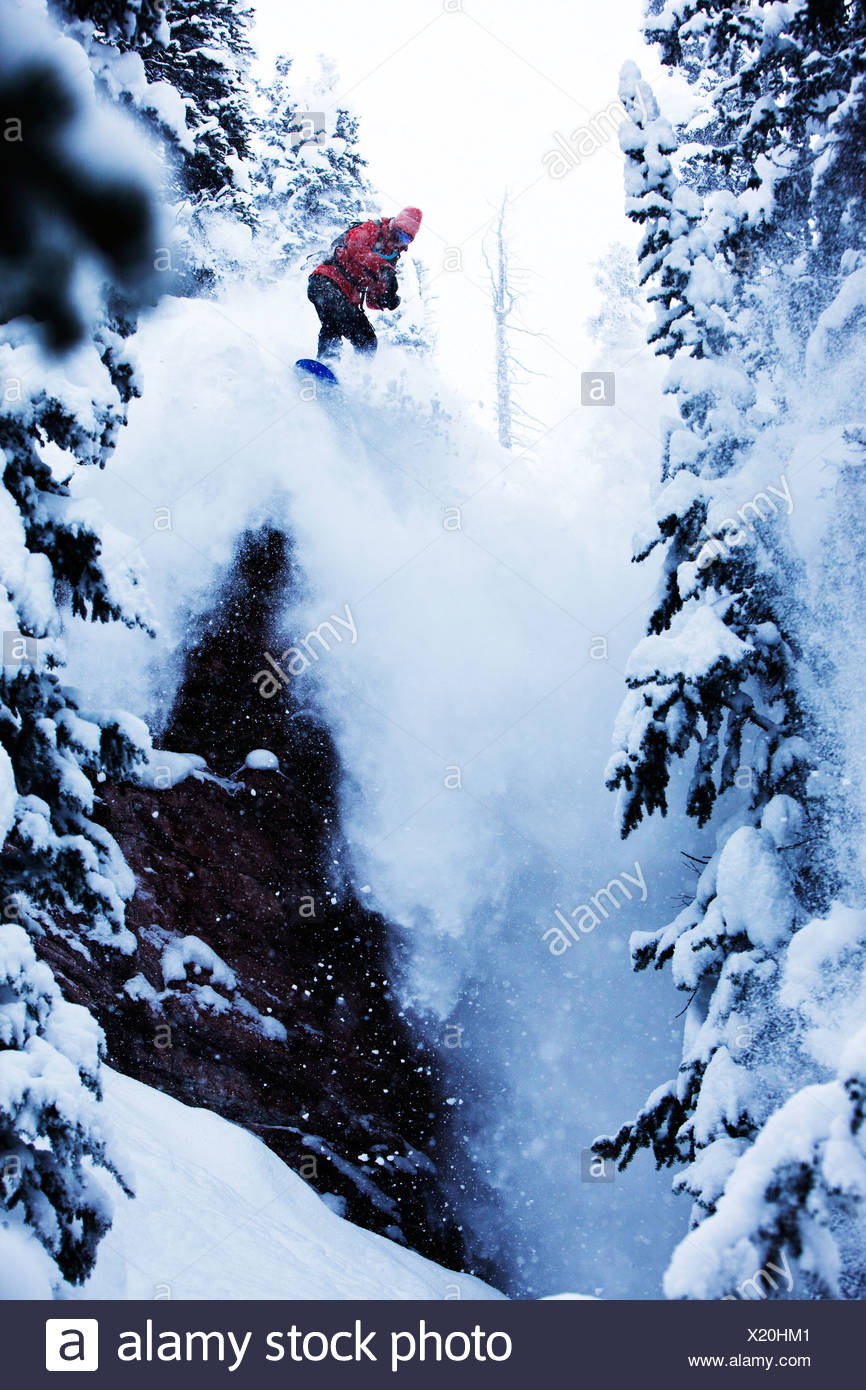 A athletic snowboarder jumping off a cliff in the backcountry on a stormy day in Colorado. - Stock Image