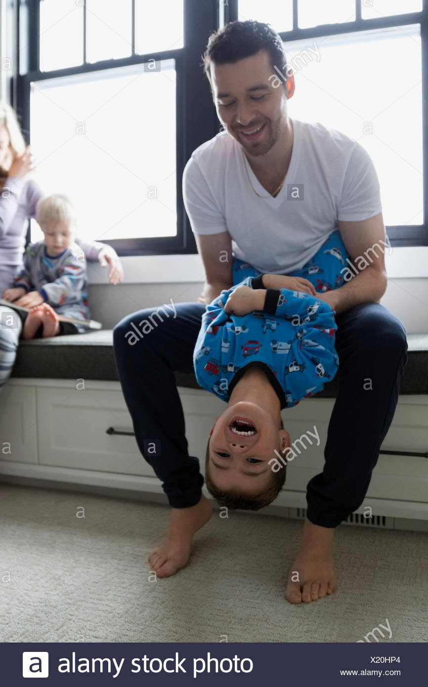 Father holding laughing son upside-down - Stock Image