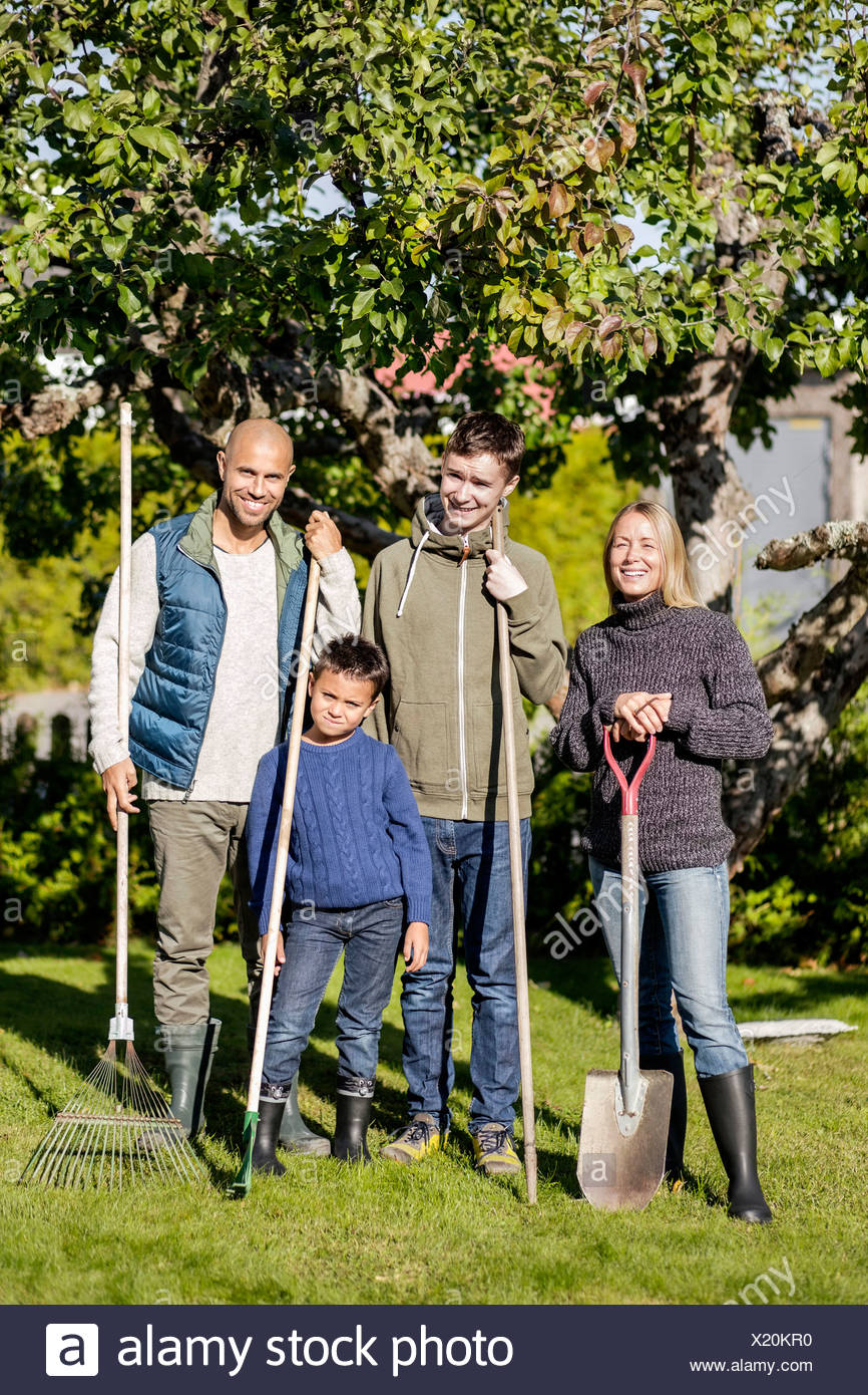 Portrait of family with gardening equipment standing at yard - Stock Image