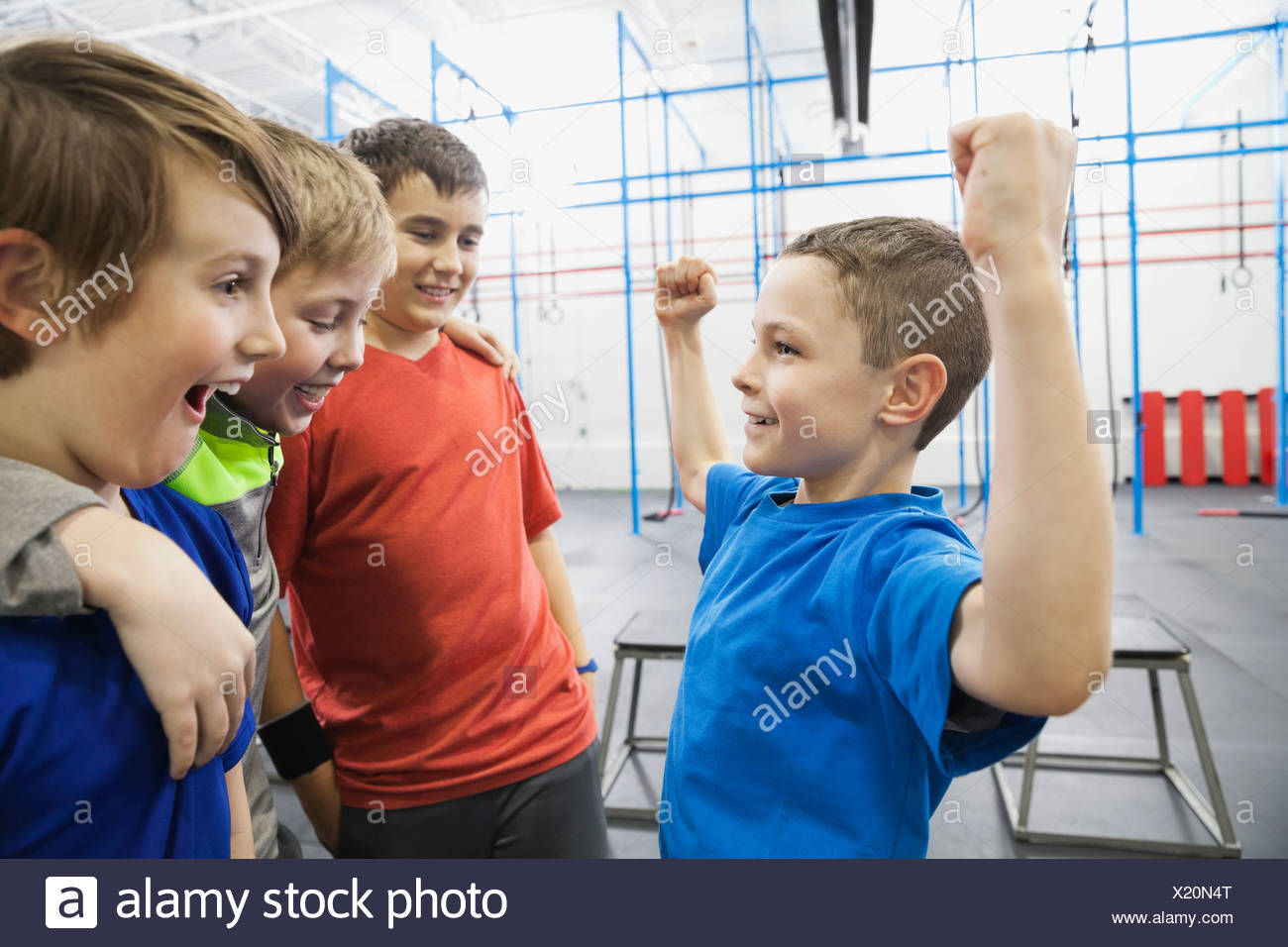 Boy showing muscles to friends in gym - Stock Image