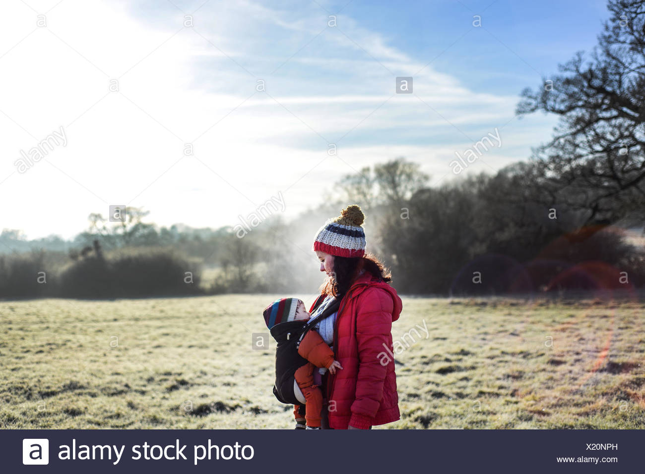 Woman in rural setting, carrying young baby in sling - Stock Image
