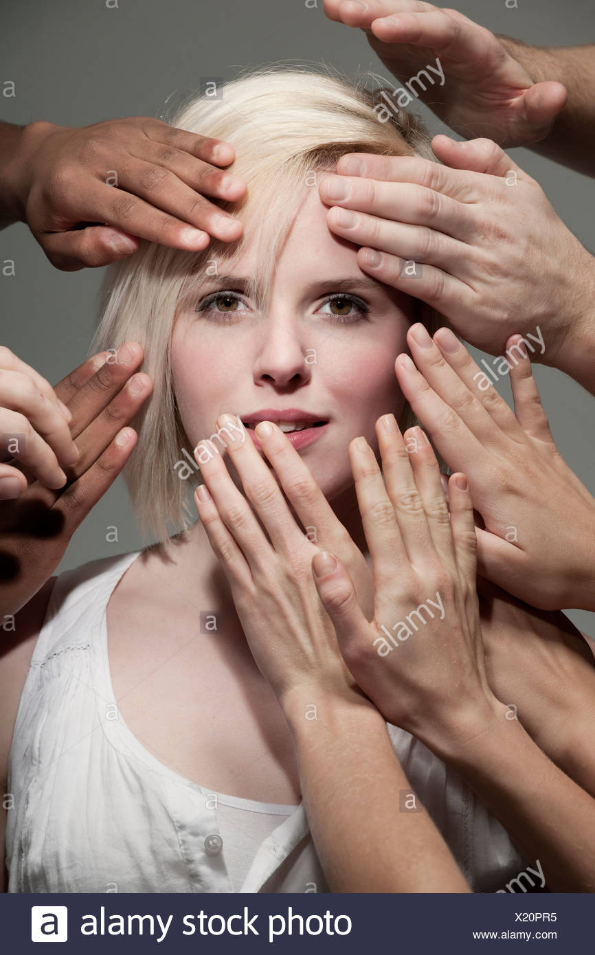 Woman being touched by many hands - Stock Image