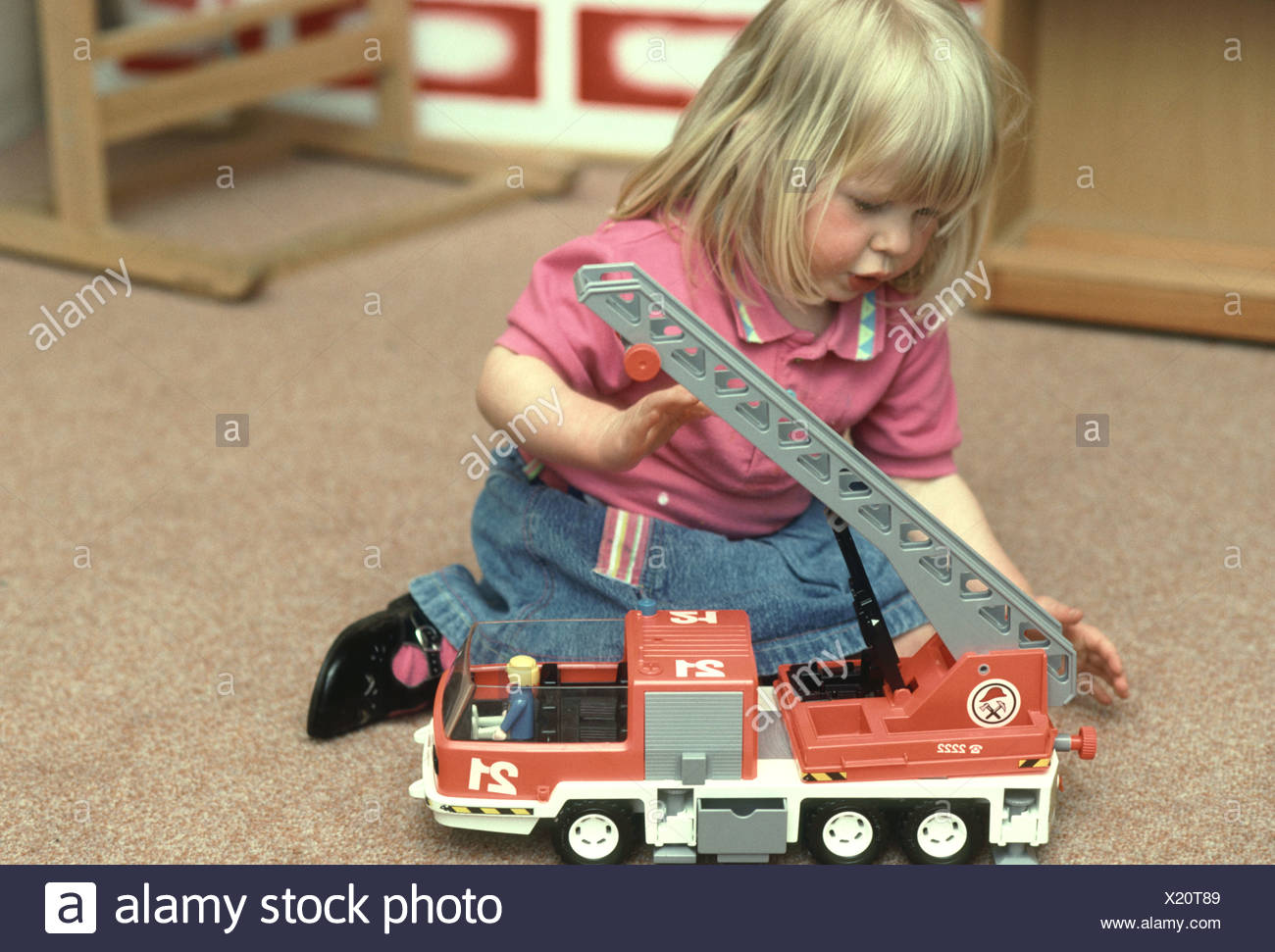 nursery school girl playing with a toy fire truck - Stock Image