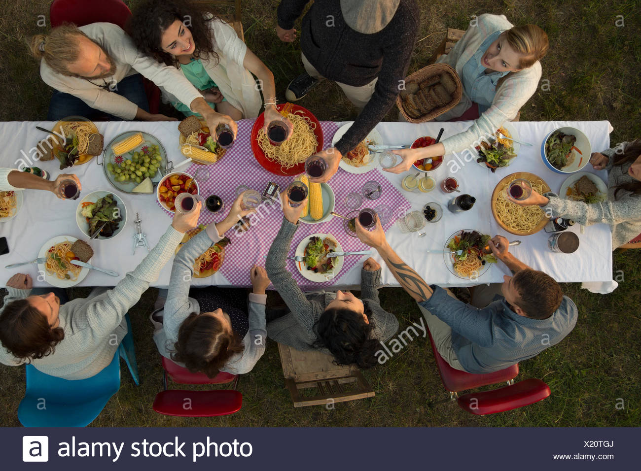 Overhead view friends toasting wine glasses at garden party dinner - Stock Image