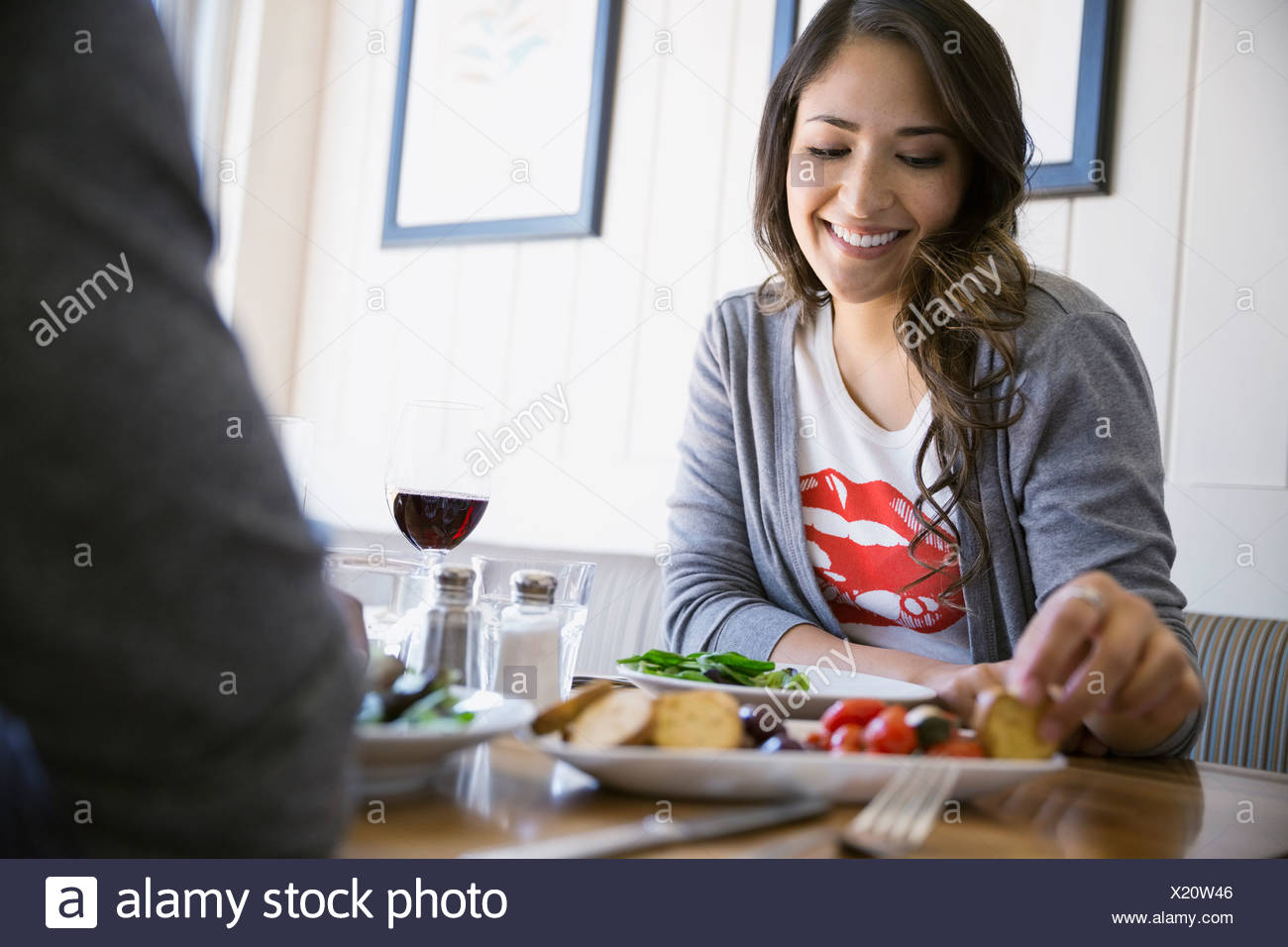 Woman eating appetizer at bistro table - Stock Image