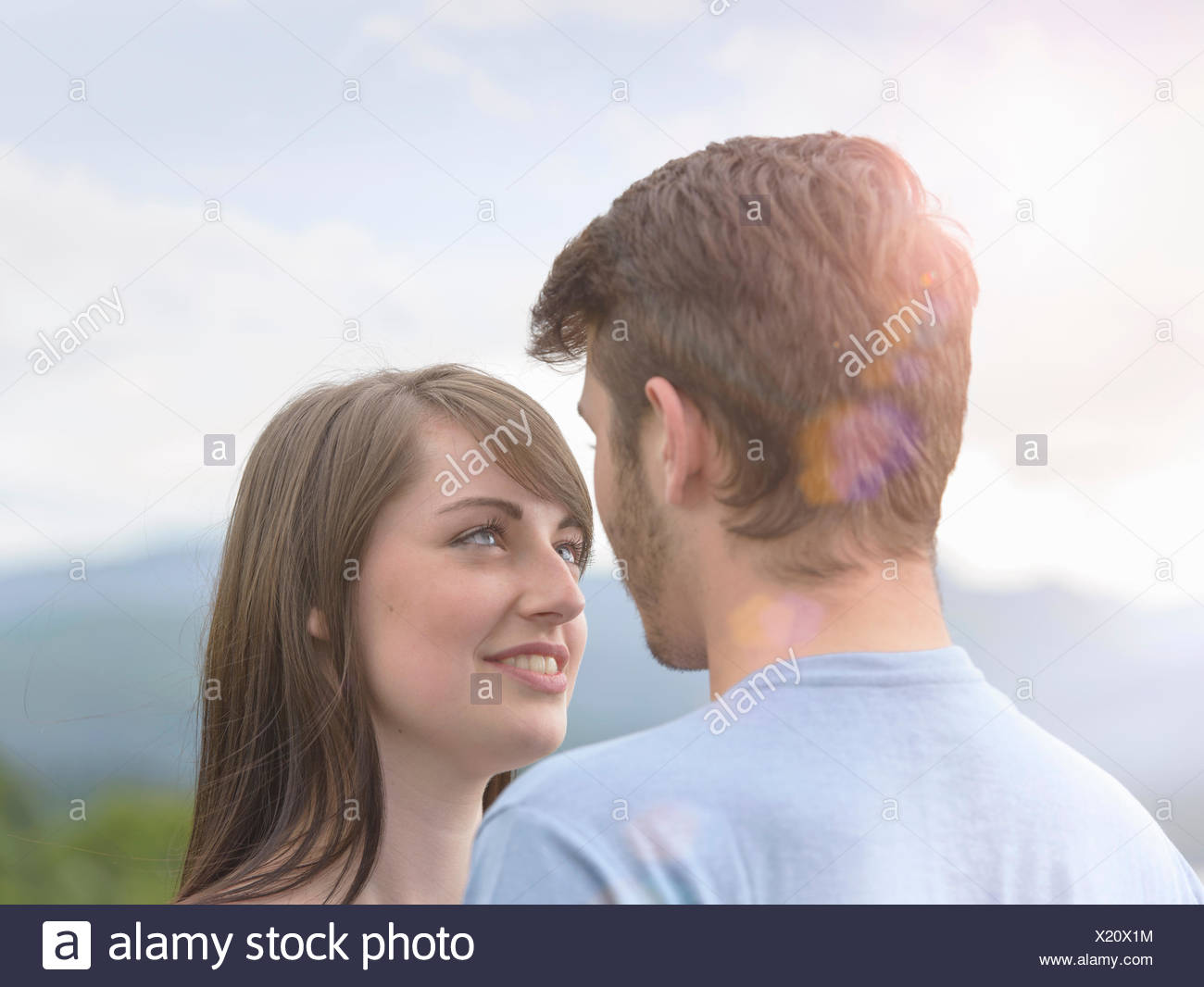 Young couple face to face under bright sunny sky - Stock Image
