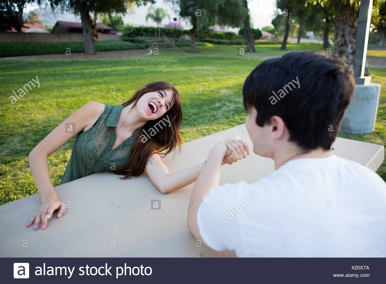 Young couple pretending to arm wrestle at picnic bench in park - Stock Image