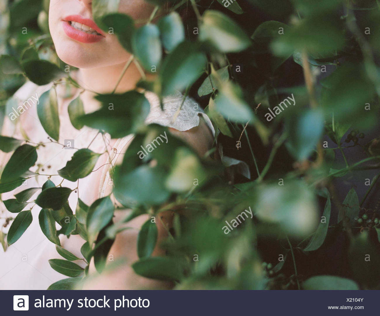 A blonde haired woman in a dress leaning against a wall with a growing vine. - Stock Image