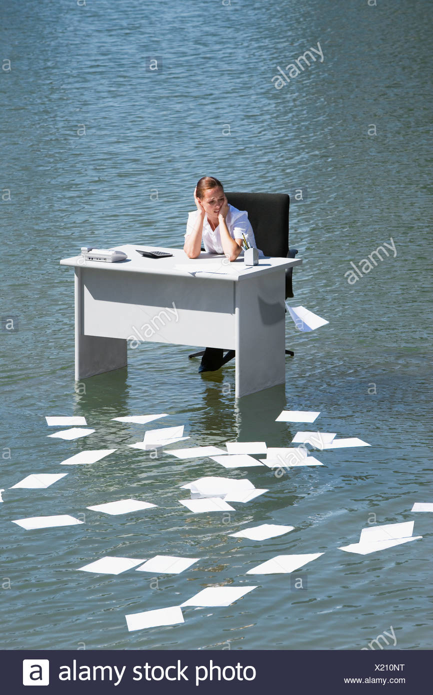 Businesswoman sitting at desk in water with paperwork floating away - Stock Image