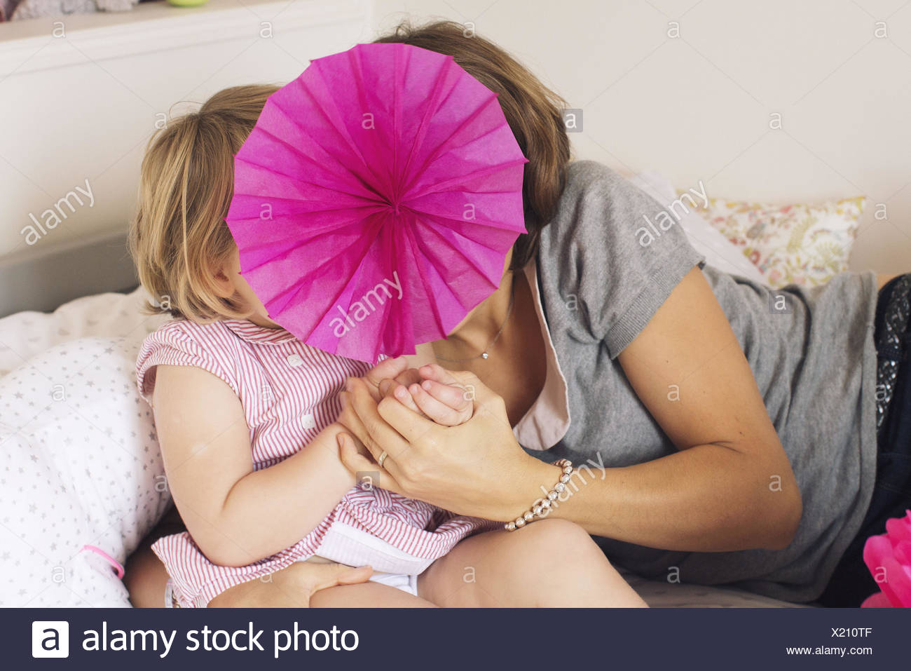 Mother and daughter hiding behind tissue paper flower - Stock Image
