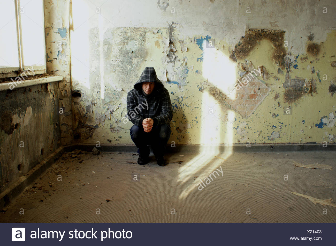 solitude,loneliness,young man,crouch - Stock Image