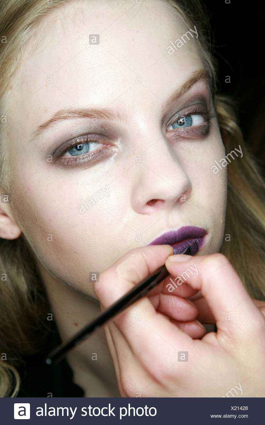 House of Holland Backstage London Ready to Wear Autumn Winter Heroin Chic: Dark purple lipstick being applied to blonde female - Stock Image