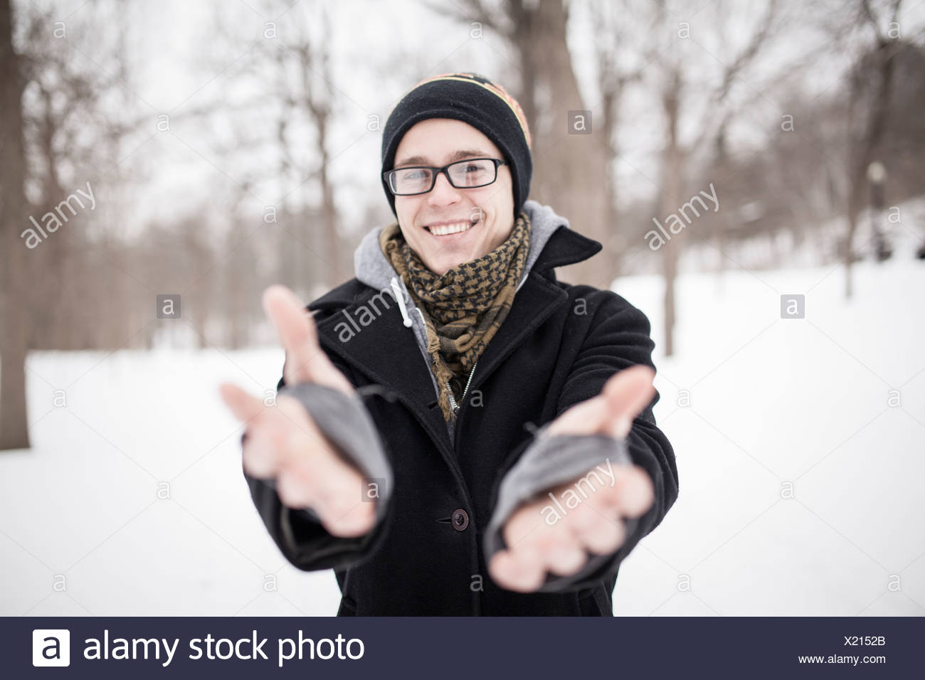 Young man standing in park reaching towards camera - Stock Image