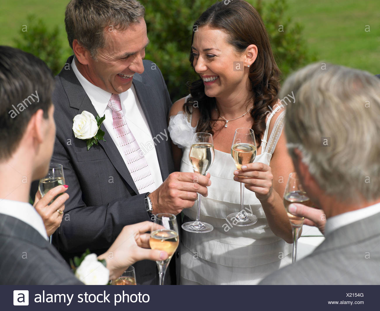 Bride and groom with wedding guests Stock Photo