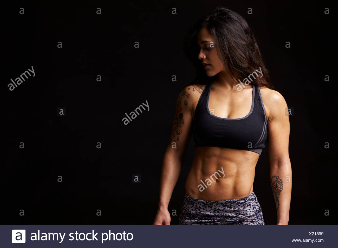 Dark haired woman in sports clothing looking down, portrait Stock Photo