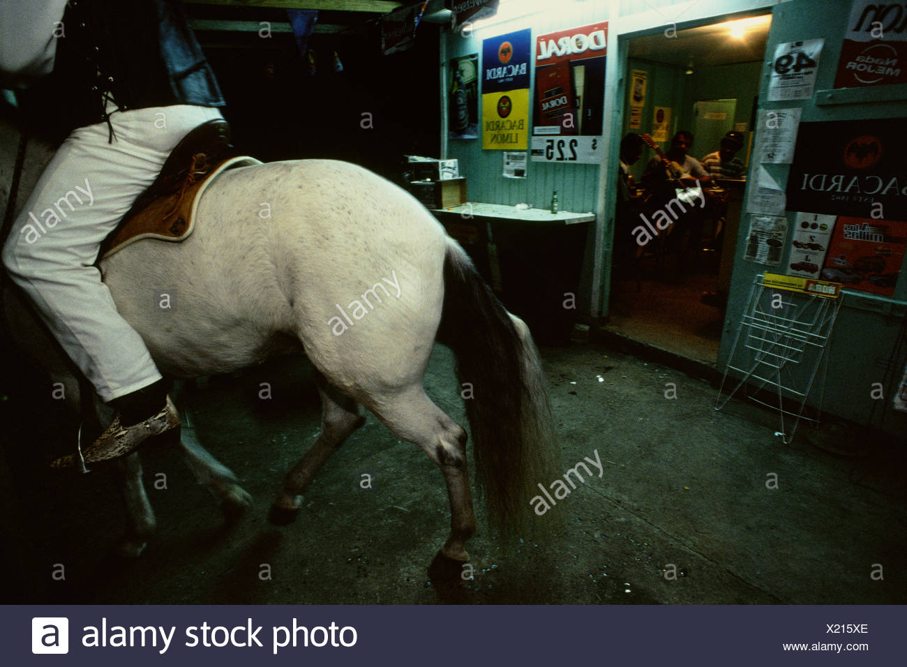 A man rides his horse and socializes outside a bar in Adjuntas. - Stock Image