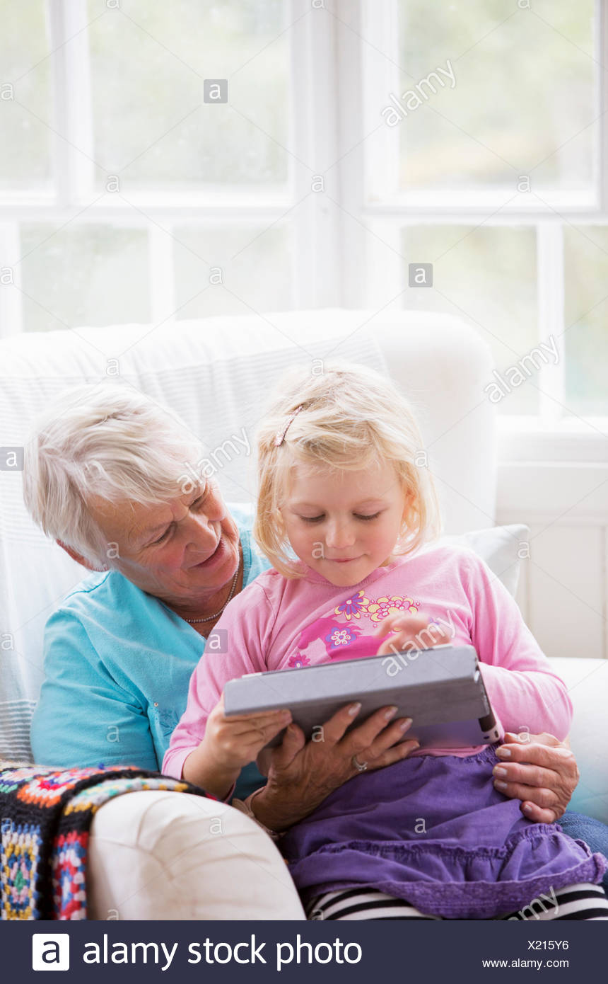 Grandmother and Granddaughter looking at a tablet - Stock Image