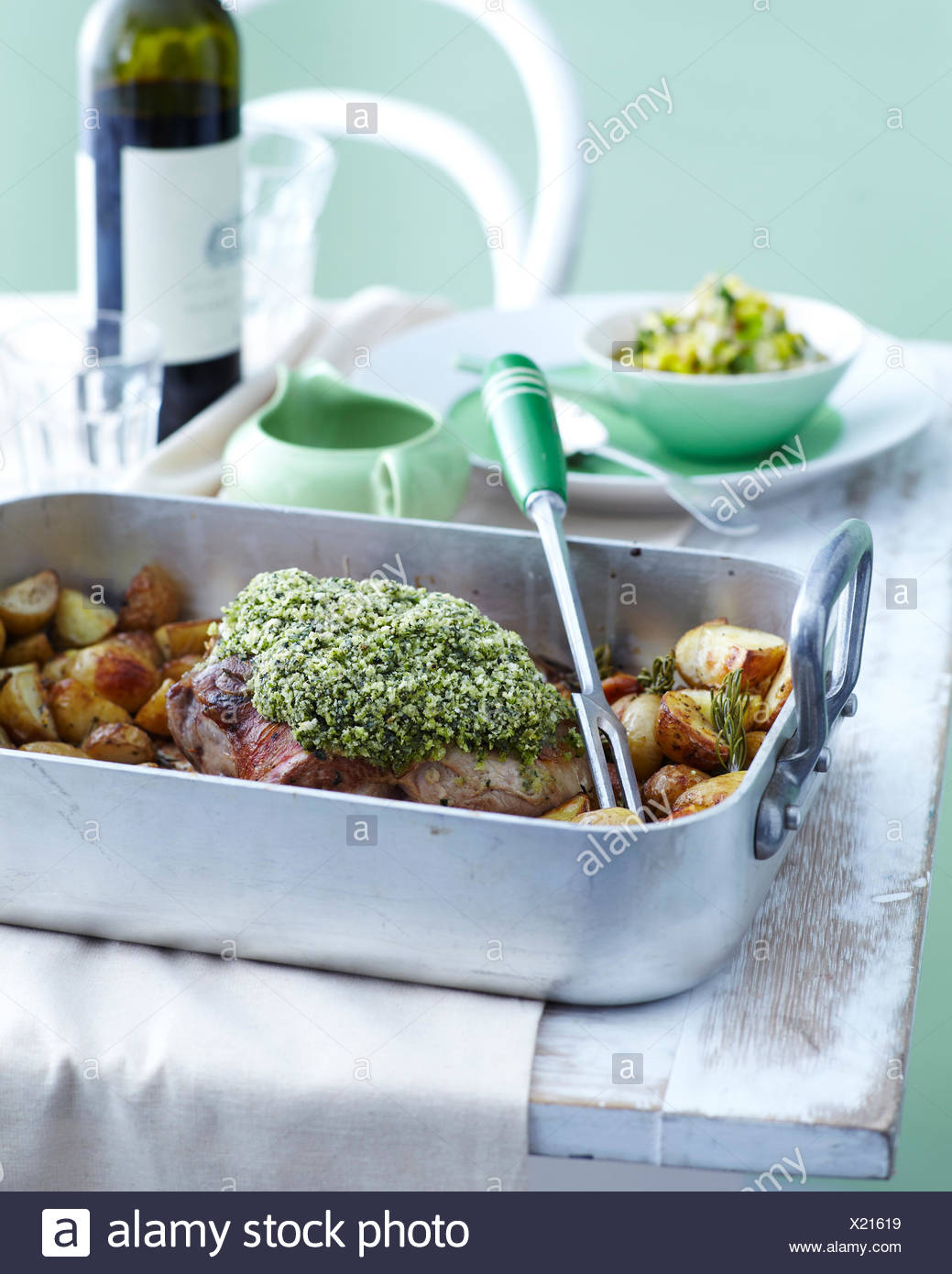 Roasting tray with roast lamb and potatoes with herb crust - Stock Image