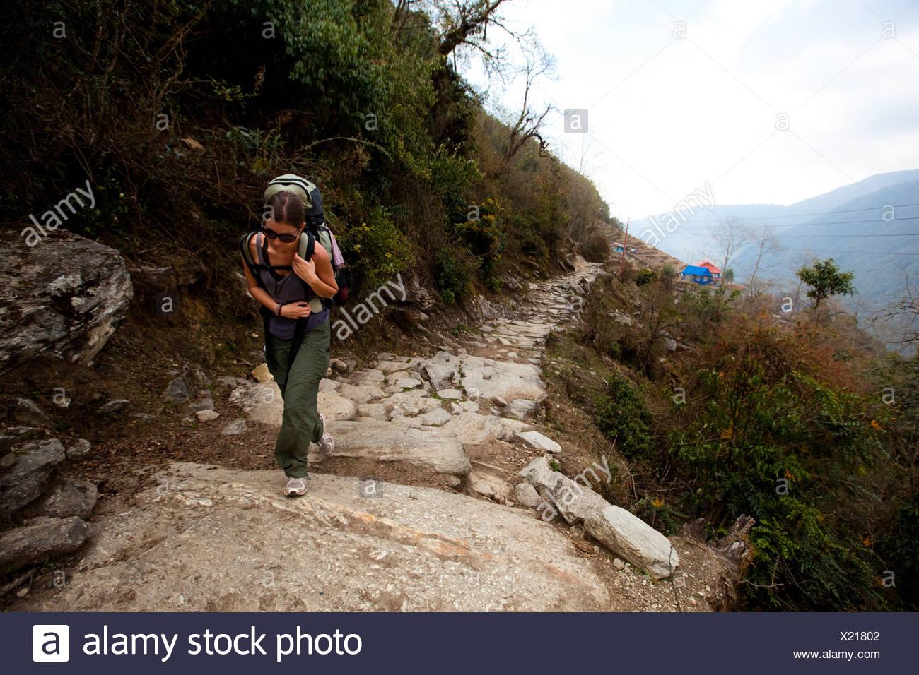 A female trekker shoulders her rucksack uphill in Nepal. - Stock Image