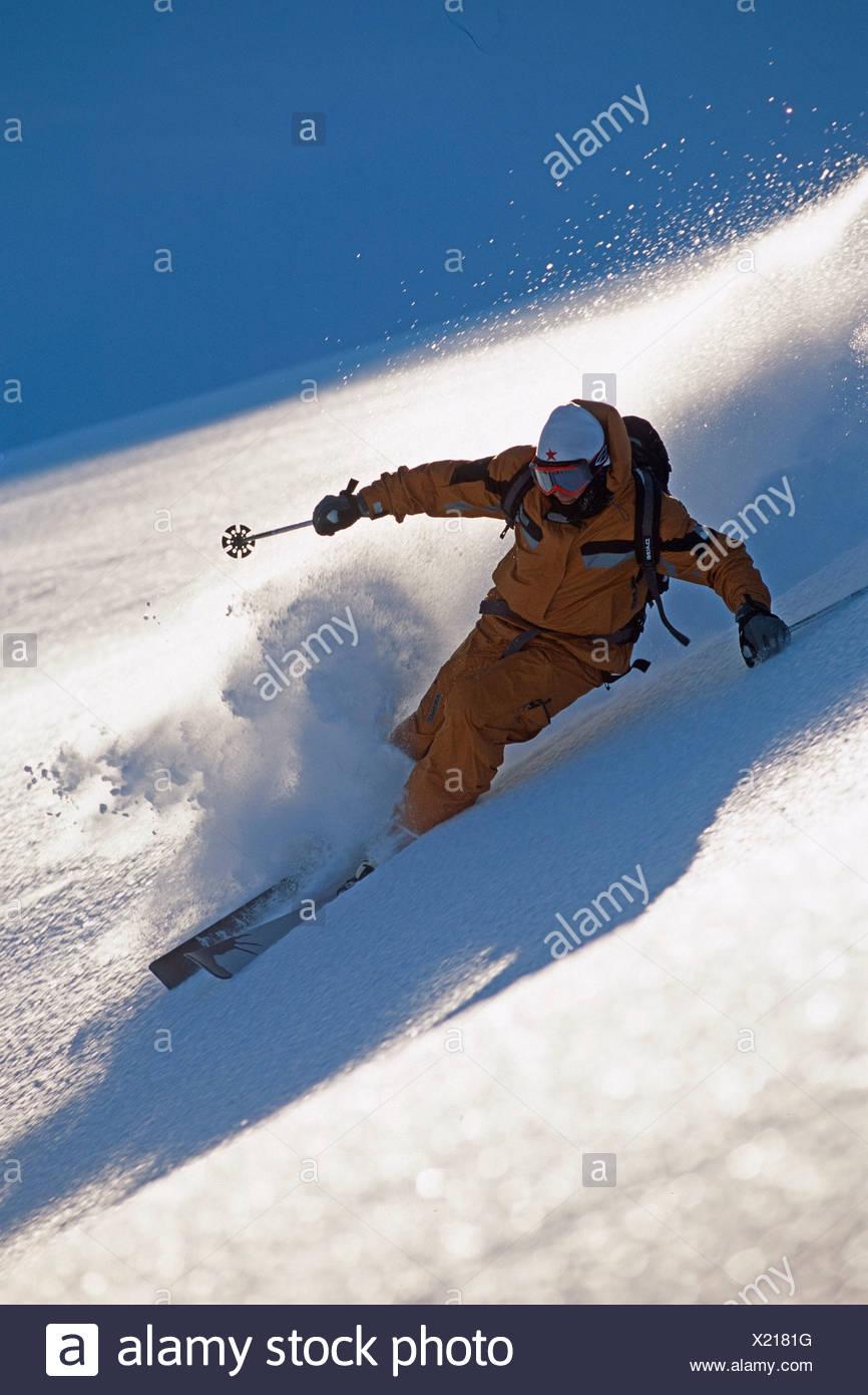 Heli-skier cuts turn on high mountain slope Chugach Mtns Southcentral Alaska Winter Backlit - Stock Image