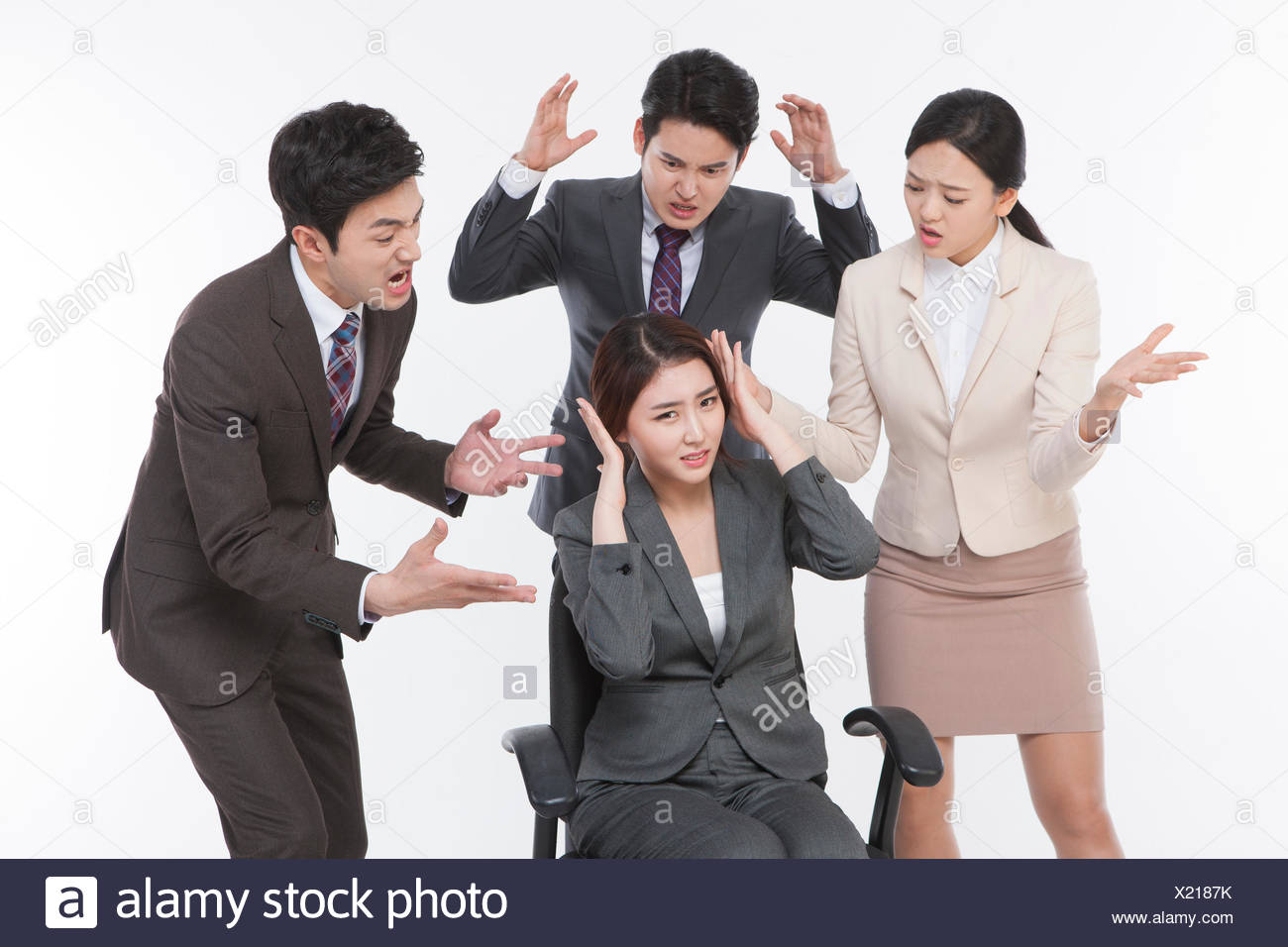 One stressful business woman and three business people angry at her - Stock Image